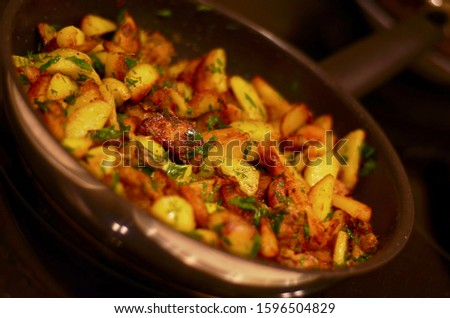 Potatoes fried with meat and herbs in a shiny frying pan against a dark background. #1596504829