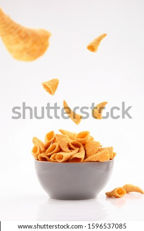 sparse golden cone corn chips in gray bowl isolated on white background #1596537085