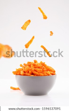 sparse stick corn chips in gray bowl isolated on white background #1596537091