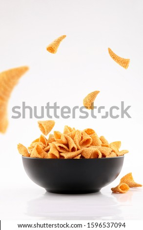 sparse golden cone corn chips in black bowl isolated on white background #1596537094