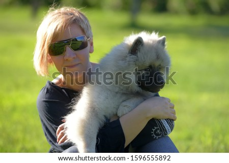 young blonde woman in summer sunglasses with keeshond wolfspitz puppy on a background of green grass #1596555892