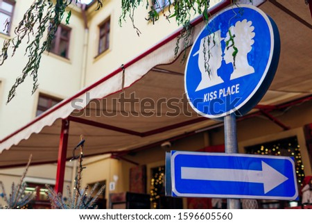 Kiss place sign in Lviv outdoor cafe. Kissing couple picture and arrow. Traveling and tourism, places of interest #1596605560