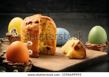 Easter cake on a cutting board and colored eggs - traditional easter breakfast