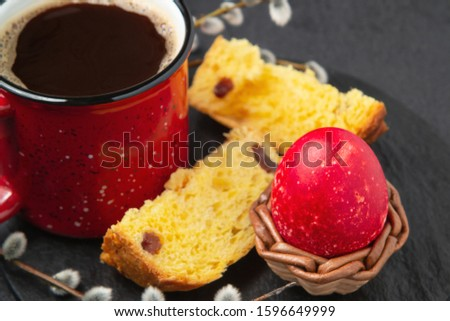 Red Easter egg, a slices of Easter cake and a cup of coffee on a cutting board on a dark table - traditional Easter breakfast