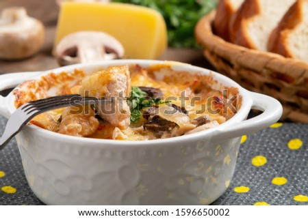 Casserole with chicken, mushrooms and cheese, known in Russia as julienne in white bowl with herbs on a kitchen towel, close up