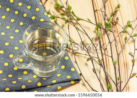 Birch juice on kitchen towel on a table in a glass mug, next to a branch of birch with young leaves