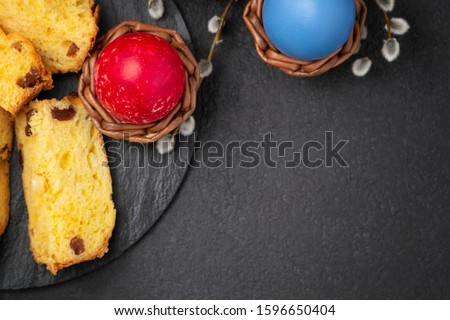 Painted Easter eggs in wicker coasters, pieces of Easter cake on a cutting board on a dark table - traditional Easter breakfast, top view, flat lay