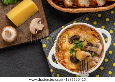 Casserole with chicken, mushrooms and cheese, known in Russia as julienne in white bowl with herbs on a kitchen towel, top view, flat lay
