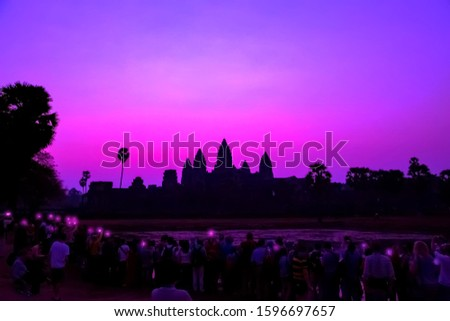 Tourist taking picture smartphone Angkor Wat temple Panorama Mist sunrise tropical morning violet on water pond sky background. Holy place in Asain. Popular tourist attraction ancient temple.