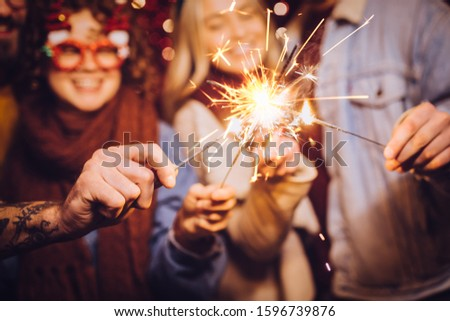 Close view of sparklers. Group of happy friends celebrating New Year with sparklers. New year party. #1596739876