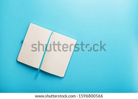 Open notebook, diary with blank and blank pages on a blue background, top view. Layout for design, free space #1596800566