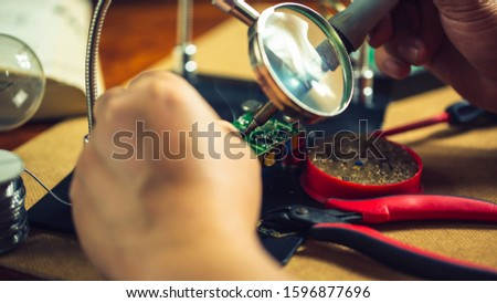 Hands of man holding solder iron  soldering the pin on electronics circuit board,  DIY hobbies and electrician workshop concept. #1596877696