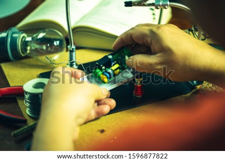 Hands of man holding solder iron  soldering the pin on electronics circuit board,  DIY hobbies and electrician workshop concept. #1596877822