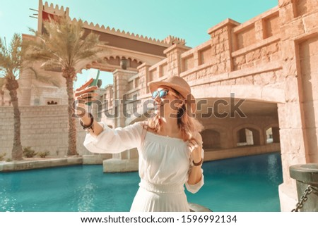 Happy asian girl in white dress taking selfie photo on her smartphone against background of middle eastern old town. Travel and vacation in Dubai and Arab Emirates concept