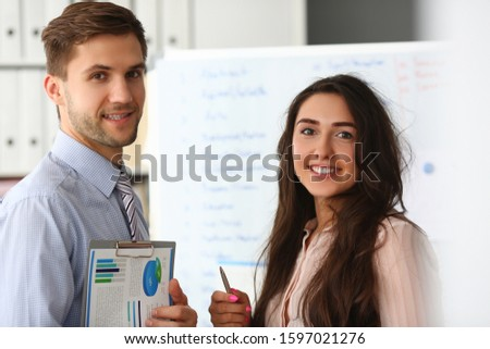 Portrait of happy co-workers posing on camera. Smiling employers with diagrams. Board with information in private office. Business growth and finance concept #1597021276