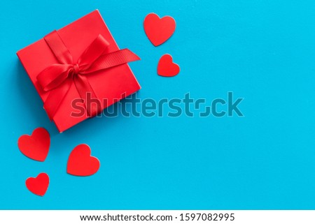 Gift to a sweetheart on Valentine's Day. Red present box near hearts on blue background top-down copy space #1597082995