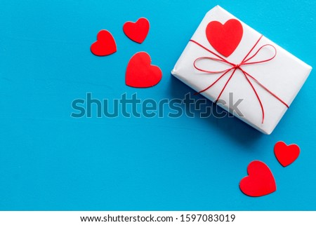 Valentine's Day gift. Present box near paper hearts on blue background top-down copy space #1597083019