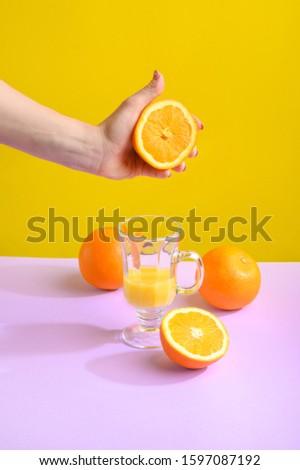 Female hand holding crushes orange and juice. #1597087192