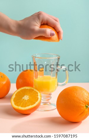Creative and fashionable photo, pastel colors. Female hand crushes orange, juice. #1597087195