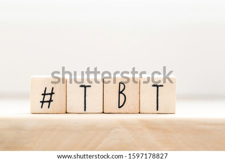Wooden cubes with Hashtag tbt, meaning Throwback Thursday near white background social media concept close-up