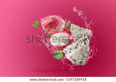 Water Splashing on Dragon Fruit or Pitaya over pink background.