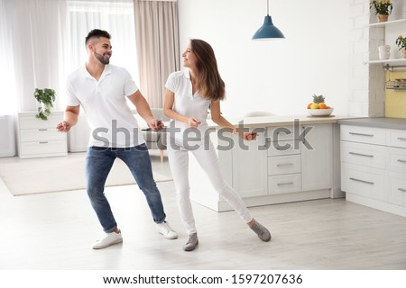 Lovely young couple dancing in kitchen at home #1597207636