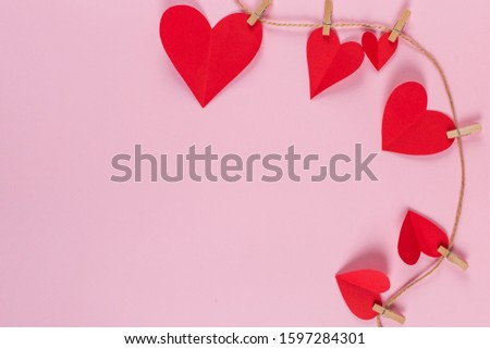 The concept of the preparation for Valentine's Day. Red hearts are held by clothespins on a jute rope, on a pink background. Copy space. #1597284301
