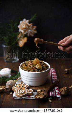 kutya, rushnyk (traditional traditional ukrainian textile), candles and christmas decor on a wooden table. hand pours honey. Christmas Slovenian food #1597351069