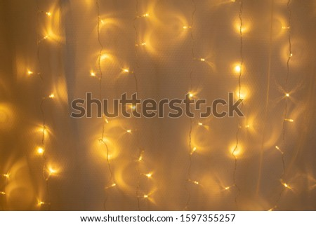 Christmas wall with curtains decorated with glowing garlands of yellow color glows with beautiful reflections. Cozy winter home. #1597355257