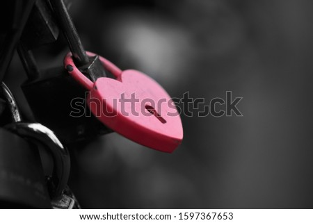 The red heart shape padlock hanging in the middle of many blurred padlocks that around and all are at the fence of the bridge in Paris, France. Concept Padlocks Love forever. Valentine. Royalty-Free Stock Photo #1597367653