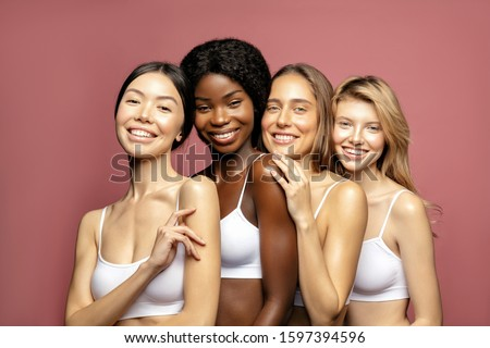 Overjoyed Multi Ethnic Group of Womans with diffrent types of skin standing together and looking on camera. Diverse ethnicity women - Caucasian, African and Asian against pink background #1597394596