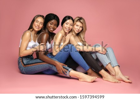 Multi Ethnic Group of Womans with diffrent types of skin sitting together and looking on camera. Diverse ethnicity women - Caucasian, African and Asian against pink background #1597394599
