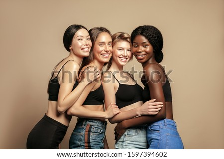 Multi Ethnic Group of Womans with diffrent types of skin standing together and looking on camera. Diverse ethnicity women - Caucasian, African and Asian against beige background #1597394602