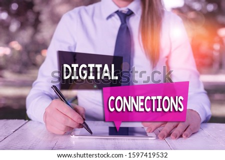 Handwriting text Digital Connections. Concept meaning the online way to explore and build relationships Female business person sitting by table and holding mobile phone. #1597419532