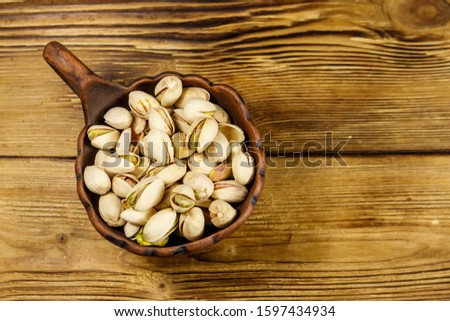 Pistachio nuts in ceramic bowl on a wooden table. Top view #1597434934