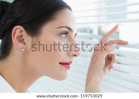 Close-up side view of a young business woman peeking through blinds at office #159753029