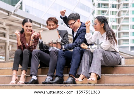 Group of business people feeling excited together with raised up hands for successful the project. Colleagues surprise positive news sitting on stairs city. Teamwork,financial and investment concept. #1597531363