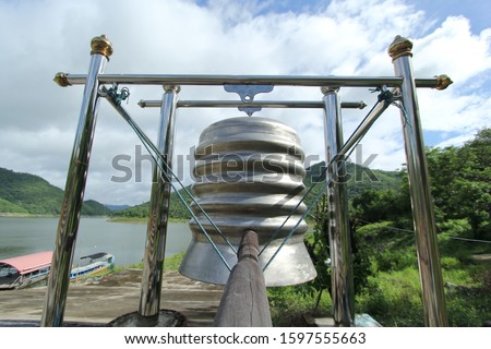 A large stainless steel bell in a Buddhist temple on the edge of the dam. #1597555663