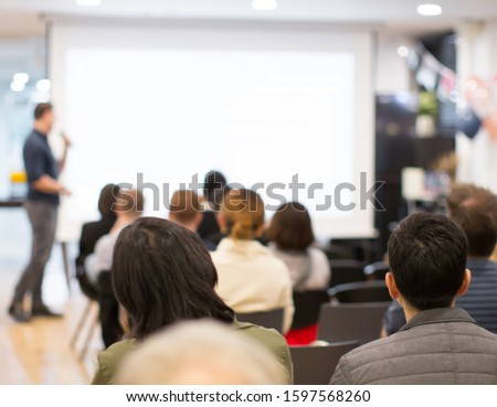Seminar with expert speaker presenting to audience in hall. Blank business presentation screen for copy space. Executive presenter giving a speech. Leadership training coach in workshop lecture.	  #1597568260