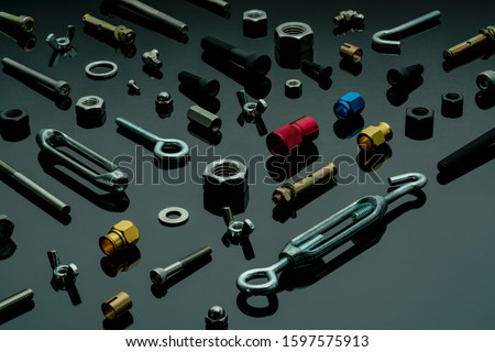 Metal bolts, nuts, and washers. Fasteners equipment. Hardware tools. Different types of nuts, bolts, and screws on table in workshop. Mechanic tools. Threaded fastener use in automotive engineering. Royalty-Free Stock Photo #1597575913