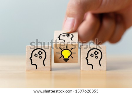 Concept creative idea and innovation. Hand flip over wooden cube block with head human symbol and light bulb icon #1597628353