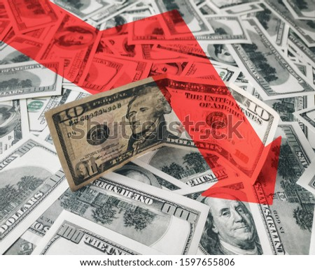 The bright red arrow icon on a background of money. The concept of changing course of US dollar on the market. Devaluation, collapse, stagnation of the economy. #1597655806