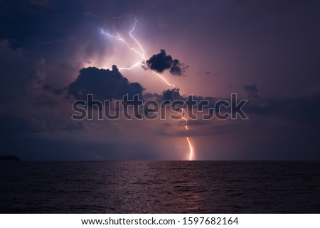 Thunderstorm and lightning in the high sea. Stormy sky with lightning flares. Nature during a sea hurricane. Photo of the night sky in a thunderstorm from the side of a sailing cruise yacht. Thailand