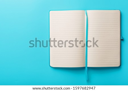 Open notebook, a book with blank and blank pages on a blue background, top view. #1597682947