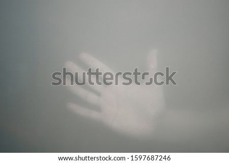 Hands behind the frosted glass. hands silhouette in the mist. loneliness concept. palm touches the window #1597687246