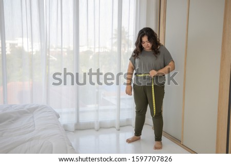 Overweight female. Plus size model. Big girl. Fat person lifestyle concept. Chubby Asian woman took a tape measure around the waist. Sorry for ineffective weight loss. Upset. Bad news. Dissatisfied #1597707826