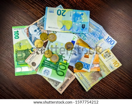 Abundance of financial and international foreign exchange represented in a concept of a pile of different currencies in paper money and metal coins #1597754212