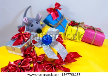 silver bow surrounded by red bows on a yellow background with a gray rat and gifts, isolate on a white background #1597758355