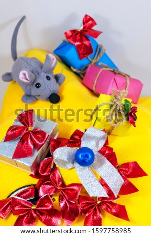 silver bow surrounded by red bows on a yellow background with a gray rat and gifts in multi-colored boxes, isolate on a white background #1597758985