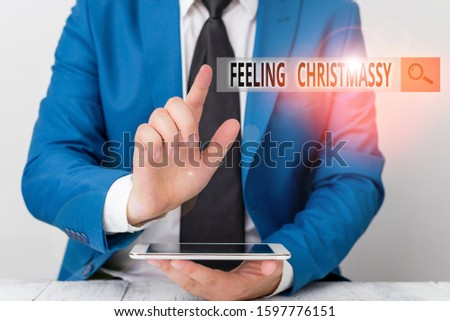 Conceptual hand writing showing Feeling Christmassy. Business photo showcasing Resembling or having feelings of Christmas festivity Businessman with pointing finger in front of him. #1597776151